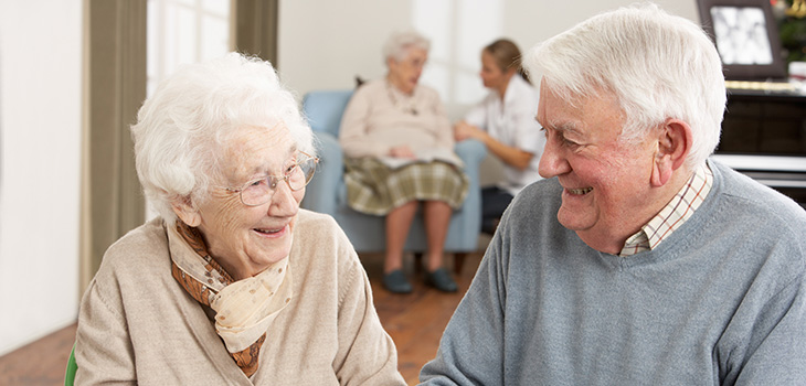 elderly couple smiling at each other in recreation room