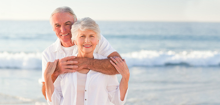 man with arms around woman in front of ocean