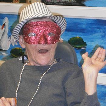 resident enjoying mardi gras celebration wearing a red mask