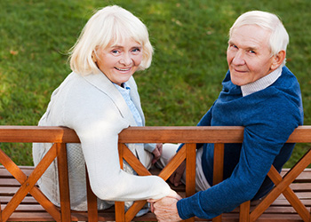 couple sitting on a wood bench holding hands with the grass behind them