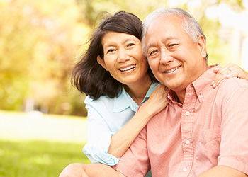 couple sitting together, smiling with the grass and trees in the background