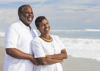 couple standing by the sea shore smiling with clouds in the sky and white foam from the waves on the shore