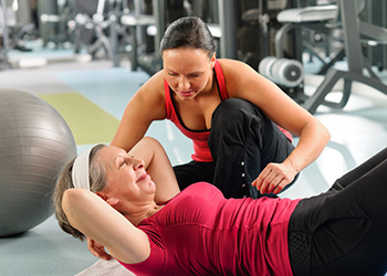 woman assisting elderly woman with sit ups with gym equipment in the background