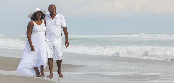 smiling couple dressed in all white taking a walk on the beach