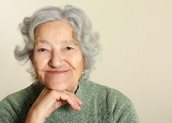elderly woman smiling with chin on hand
