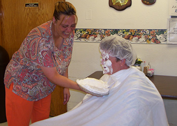 A staff member hitting another staff member in the face with a pie