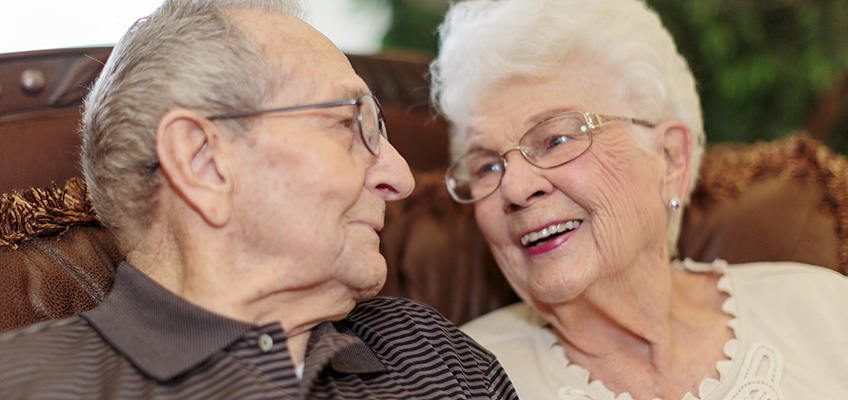 elderly couple looking at each other fondly