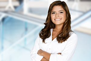 A professional woman standing with her arms folded smiling