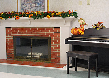 Fireplace decorated for all with a piano beside it