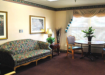 Sitting area with decorative couch, end table with plant and lamp along with seating beside the couch.
