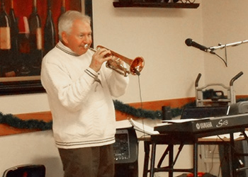 A man playing the trumpet to residents