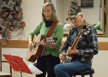 A man and woman playing guitars and singing to residents