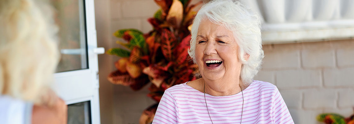 laughing woman sitting on an outdoor patio with a large potted plant