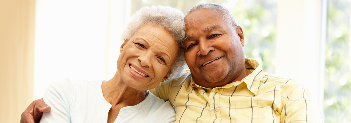 smiling elderly couple sitting in a sunny room