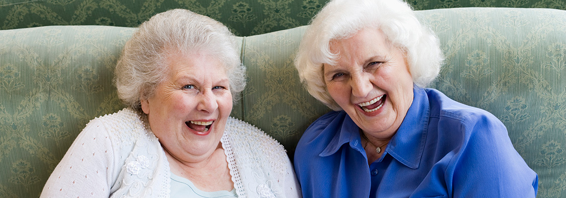 2 elderly female friends laughing while seated on a couch together